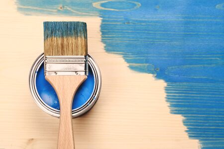 modernise: Paint brush on the can lying on wooden background. The surface is half - toned with blue color.
