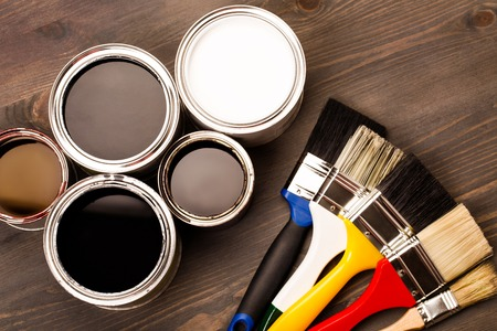 House renovation, paint cans and colored brushes on the wooden grey background