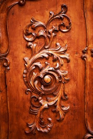 ornately: Beautiful ornately carved wooden pattern on a dark background on an antique door.