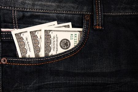 bolsa dinero: billetes de dólares que yacen en el bolsillo de jeans. El dinero de bolsillo, de cerca. Foto de archivo