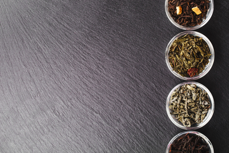 space for type: Four bowls with different types of tea: black and green, are standing on black stone textured backgroung. Place for your text. Stock Photo
