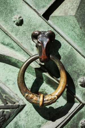 stoop: Antique and medieval wooden door knocker in the old city of Krakow, Poland.