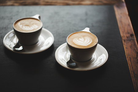 coffee froth: Two cups of cappuccino with latte art on black table. Morning coffee for couple in love. Top view.