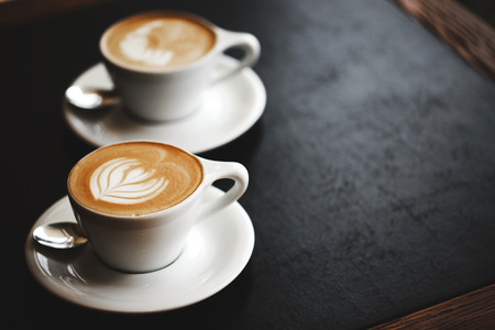 Two cups of cappuccino with latte art on black table. Morning coffee for couple in love. Top view.