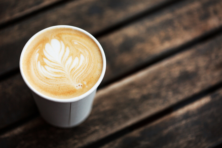 Cup of coffee to go on the wooden table with latte art. Street coffee, top view.