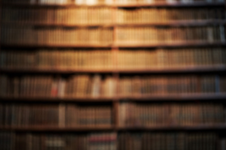 Blurred background of old books on shelves in library. Vintage books, retro style. Фото со стока - 59045287