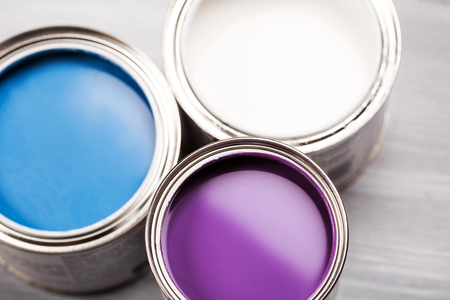 gallons: Several opened cans with paint inside. Blue, lavender or violette and white. Close up. Stock Photo