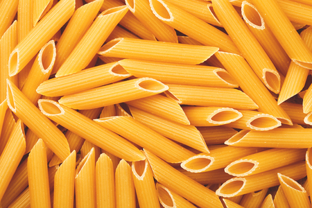 unorganized: Penne italian pasta as textured background, closeup. Stock Photo