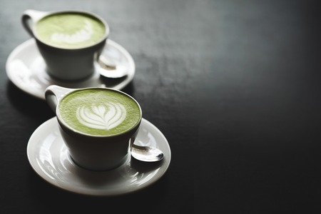retro couple: Two cups of matcha latte with latte art on black table. Top view.