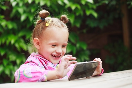 smart girl: Outdoor portrait of cute blonde toddler girl using a digital tablet or smart phone.
