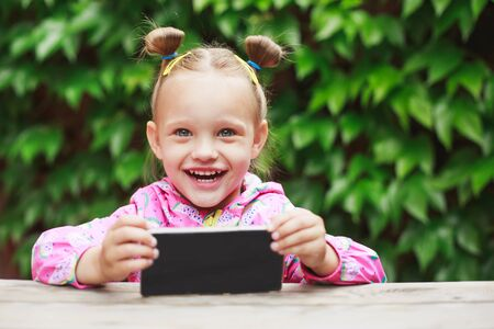 Outdoor portrait of cute blonde toddler girl, laugh and using a digital tablet or smart phone. Stock Photo