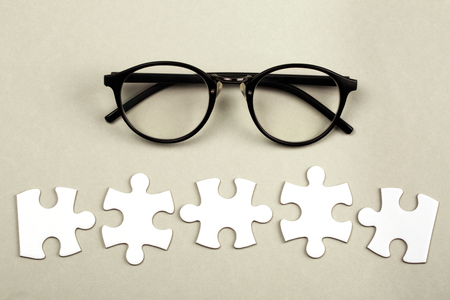 pices: Disconnected white jigsaw puzzle pices with eye glasses. Business and teamwork concept.