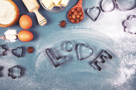 heart shaped stuff: Heart - shaped cookie cutters, flour and word Love, made with it, and other stuff for baking cookies, lying on blue background. Stock Photo
