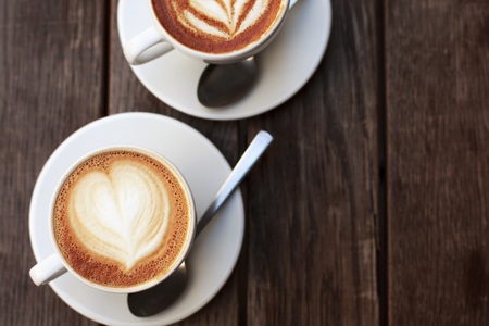 Two white cups of cappuccino with latte art on wooden table.
