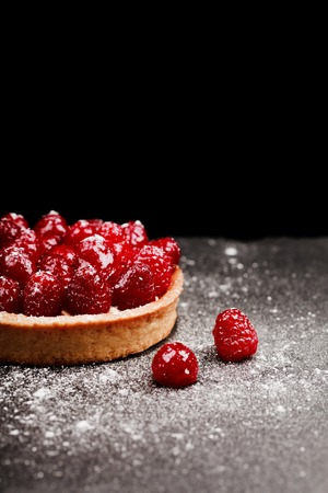 summer pudding: Tartlet with custard, fresh glazed aspberries and sieving sugar powder, served on vintage stone surface. Dark rustic style. Stock Photo