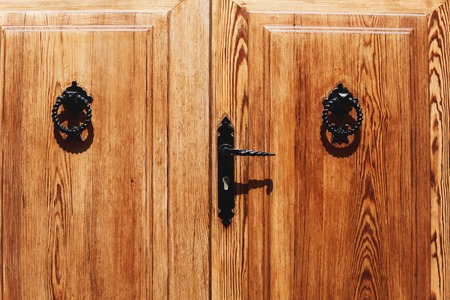 Old wooden door with bright texture on Mallorca, Spain. Metal hand, old knocker. Stock Photo
