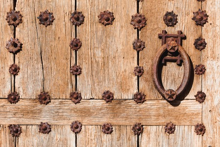 Old wooden door with bright texture on Mallorca, Spain. Metal hand, old knocker. Standard-Bild