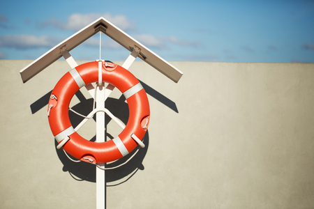 Lifebuoy on the pier on a special stand in front of a blue sky Stock Photo