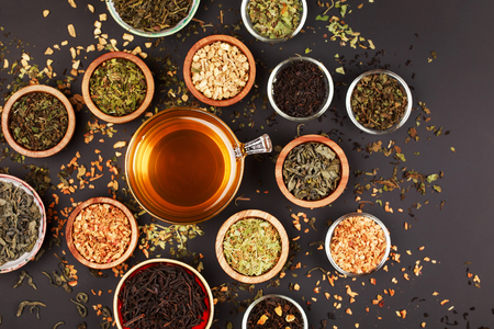 lime tree: Assortment of dry tea in little bowls, on black background. Green and black tea, mint, melissa, ginger, apple, lime tree and other components for perfect beverage.