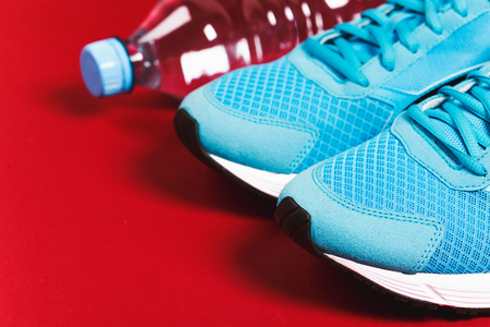 sports clothing: Blue sneakers and bottle of water on red background. Concept of healthy lifestile, everyday training and force of will.
