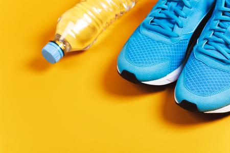lifestile: Blue sneakers and bottle of water on yellow background. Concept of healthy lifestile, everyday training and force of will. Stock Photo