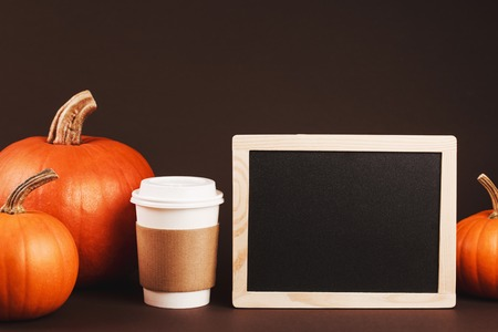 Coffee to take away with spices and pumpkin. Concept of traditional autumn spicy latte. Place for logo on brown coffee holder. Black chalk desk with wooden frame is for placing your text.