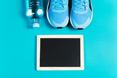 lifestile: Fitness background made of sneakers, bottled water and clean chalkboard on blue background. Concept of healthy lifestile and food, everyday training and force of will. Flat lay style of picture