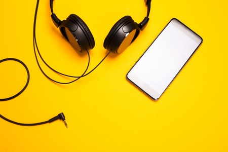 bakground: Headphones and smart pnone on colorful bakground. Concept of living with music.