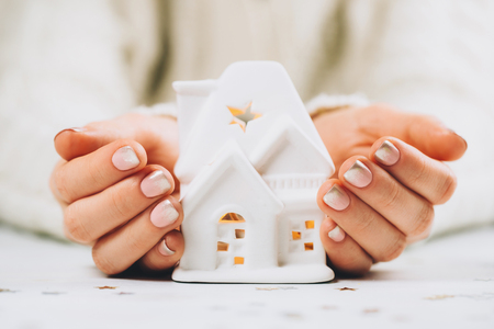 Female hands holding and saving small white house with a roof and lights.