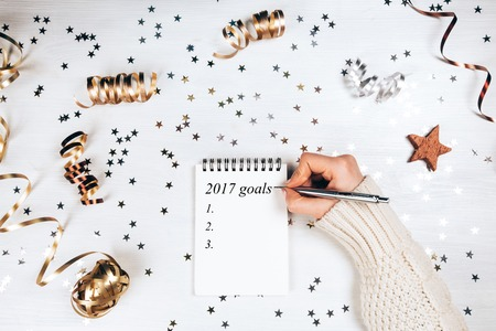 Holiday decorations and notebook with 2017 goals on white rustic table, flat lay style. Christmas planning concept. Фото со стока