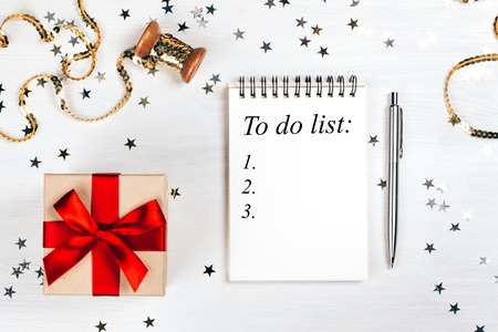 Holiday decorations and notebook with to do list on white rustic table, flat lay style. Planning concept.