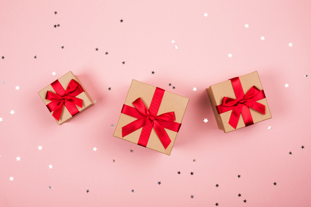 Three presents with red bow on pink background with tittle sparkles. Flat lay style.