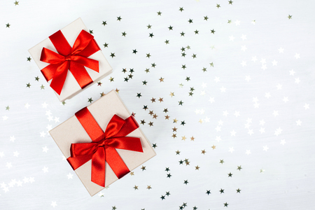 Two presents with red bow on white wooden rustic surface. Festive picture made in flat lay style with place for text.