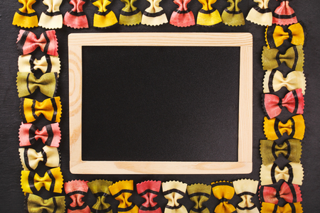 carbohydrates: Farfalle tigrate pasta forming frame on dark stone background. Place for text in a black chalkboard. Concept of slow carbohydrates for healthy nutrithion.