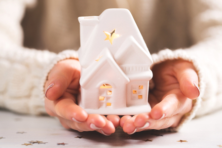 Female hands holding and saving small house Stock Photo