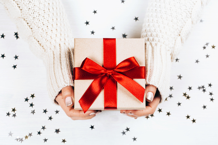 Female hands holding present with red bow