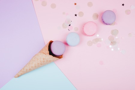 Group of pastel colorful macarons in ice cream corn on trendy pink festive background.