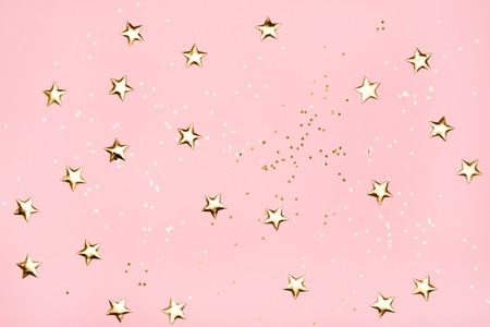 Golden stars glitter on pink background. 免版税图像