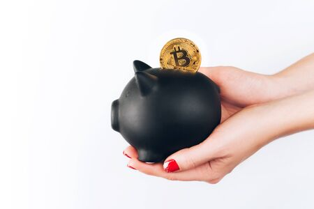 Womans hands with bitcoin in piggy bank