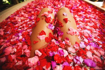 Woman in bath with petals.