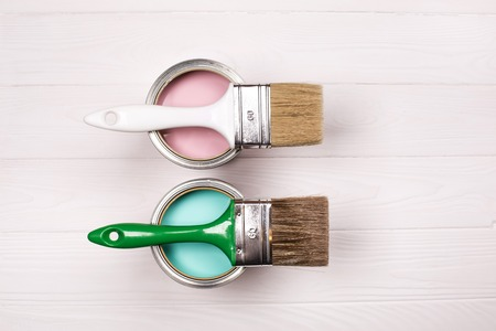 Two pink and blue open paint cans and brush on white wooden background. House renovation concept. Reklamní fotografie - 114517489