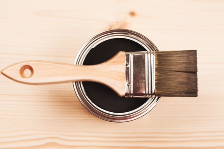 Paintbrush and a newly opened can of grey paint on wooden surface Standard-Bild - 114557252