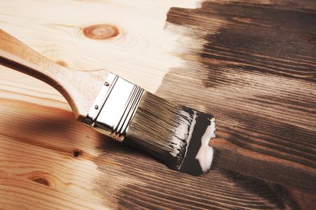 Grijze kleur schilderen op houten tafel of hek of muur, of meel, gebruik voor huisdecoratie. Renovatie huis. Half geverfd oppervlak. Uitstrijkje van kwast.