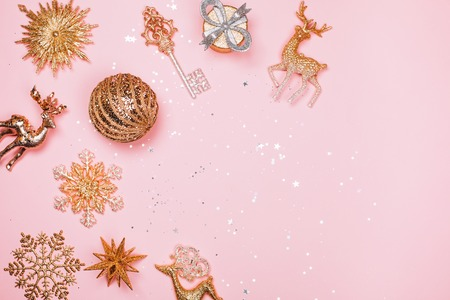 Golden beautiful sparkling christmas decorative toys on pastel pink background. Place for text. Festive concept. Stock Photo