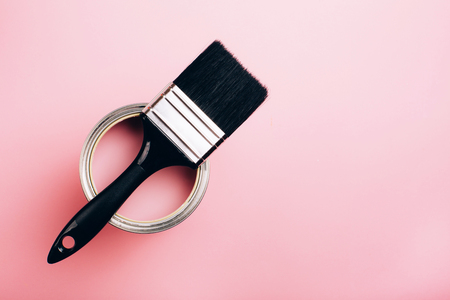 Brush with black handle on open can of pink paint on pastel background. Renovation concept. Top view.
