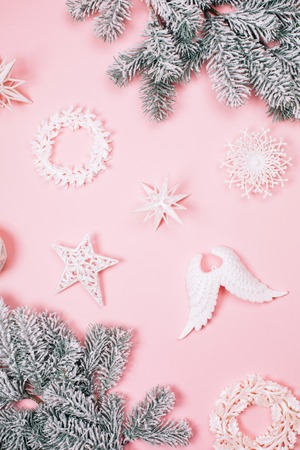 White beautiful christmas decorative toys with snow fir-tree on pink pastel background. Festive concept. Stock Photo