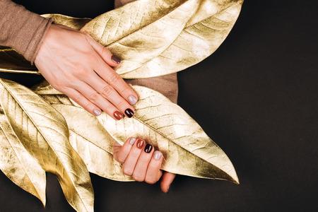 Holiday beautiful manicure with golden decorations. Dark Philosophy. Standard-Bild