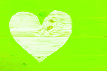 Heart shape of natural wooden background surrounding freshly painted ufo green surface. Renovation concept.