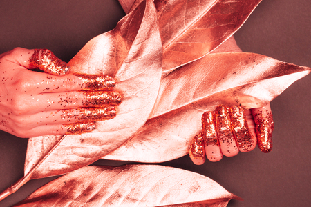 Manicure with glittering fingers. Art fashion inspired by Living Coral - colot of the Year 2019. Фото со стока