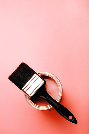 Brush with white handle on open can of Living Coral paint on trendy pastel background. Color of the year 2019. Main trend concept. Standard-Bild - 115032778